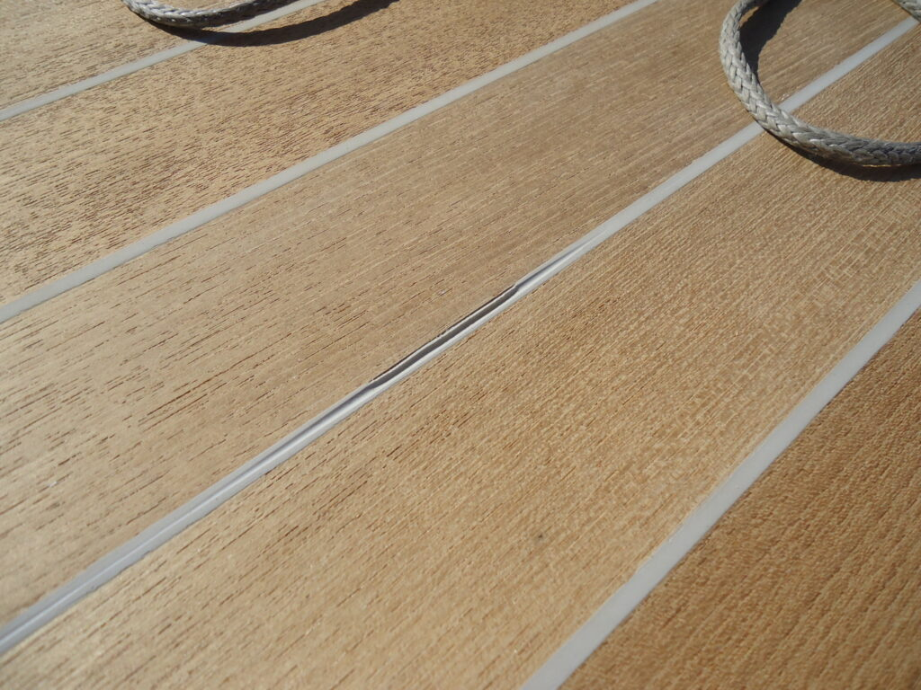 Image of teak deck with gray caulking that has been sanded too early and seam is deformed and separating