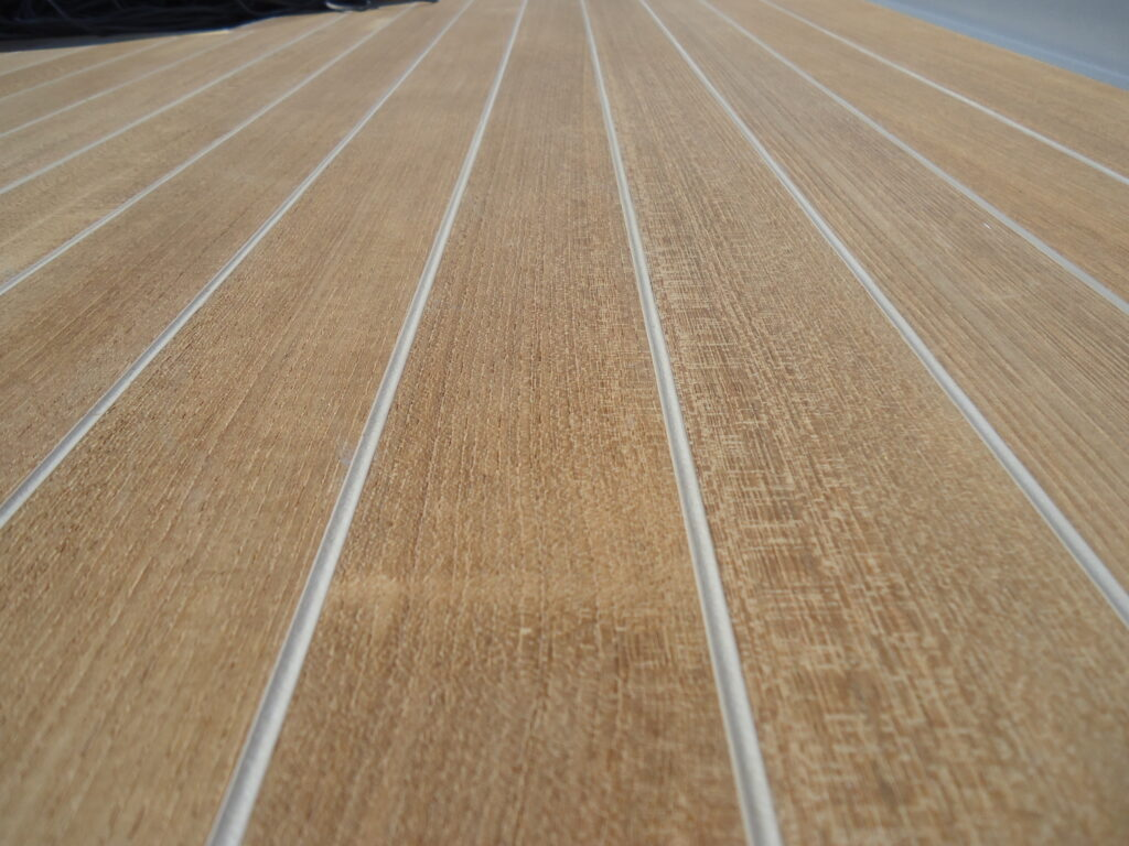 Closeup of teak decking gray seams that are underfilled below the surface of the teak