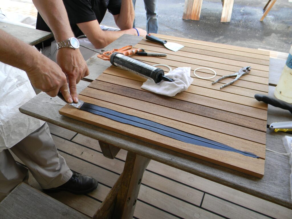Proper application of caulk to teak deck seams demonstration