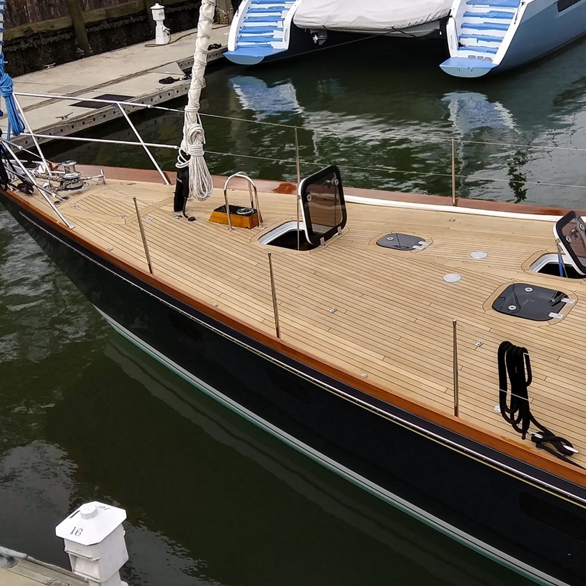image of freshly sanded teak deck bow of sailboat