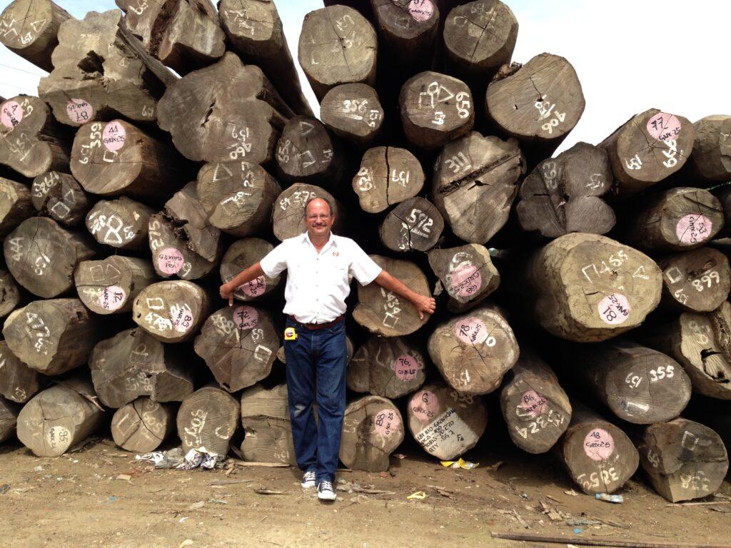 teak decking systems employee standing in front of Burmese teak logs in Myanmar